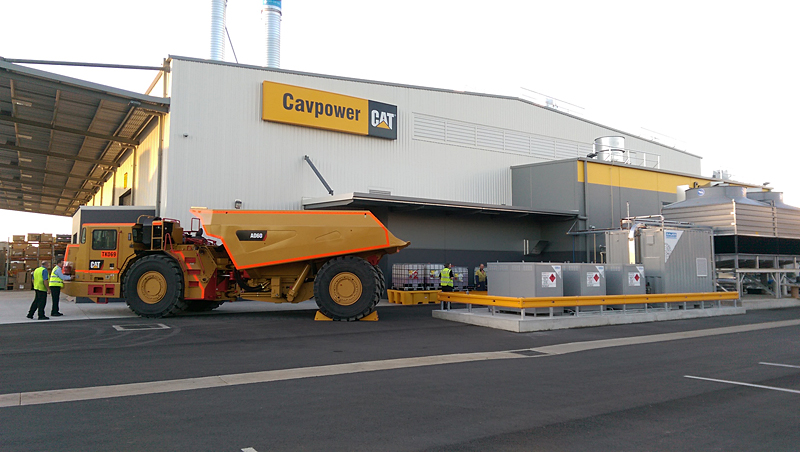 "One of CAT's ""smaller mining vehicles"" parked next to BAUER's CNG45 compression and storage equipment"